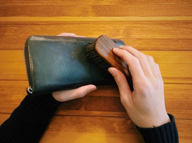 革財布についたホコリをブラシで落としている