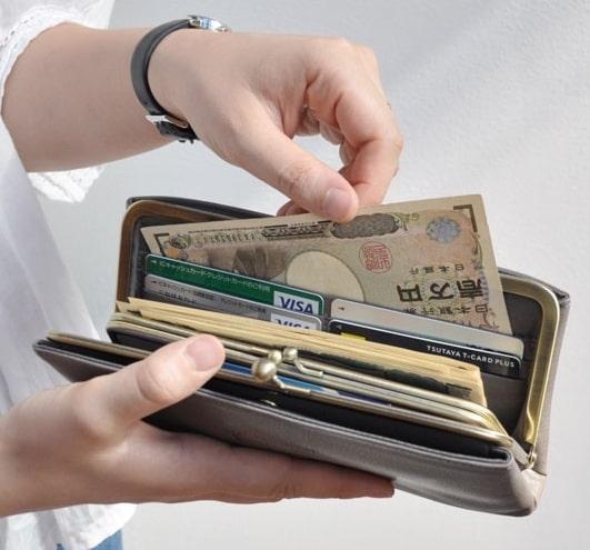 クレドランのレディースがま口財布から紙幣を取り出している